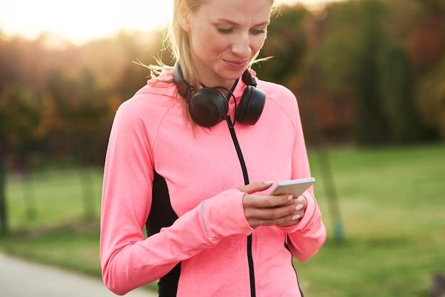 Athlète féminine utilisant un téléphone portable pendant l'entraînement de jogging