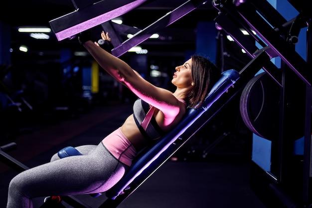 Athlète femme d'âge moyen fit attrayant, faire des exercices sur les muscles pectoraux dans simulateur. machine de gym