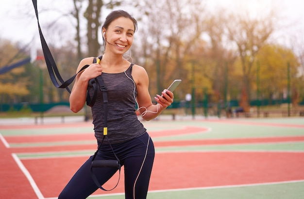 Athlète fille s'entraînant à l'aide de trx sur terrain de sport. une jeune femme adulte de race mixte fait de l'exercice avec un système de suspension. mode de vie sain. terrain de jeux extérieur qui s'étend.