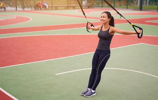 Athlète de fille s'entraînant à l'aide de trx sur le terrain de sport. race mixte jeune femme adulte faire de l'exercice avec système de suspension. mode de vie sain. terrain de jeux en plein air qui s'étend.