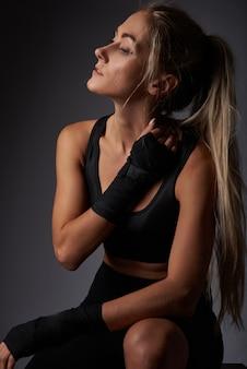 Athlète fille en vêtements de sport noir avec des bandages sur ses bras au repos après l'entraînement