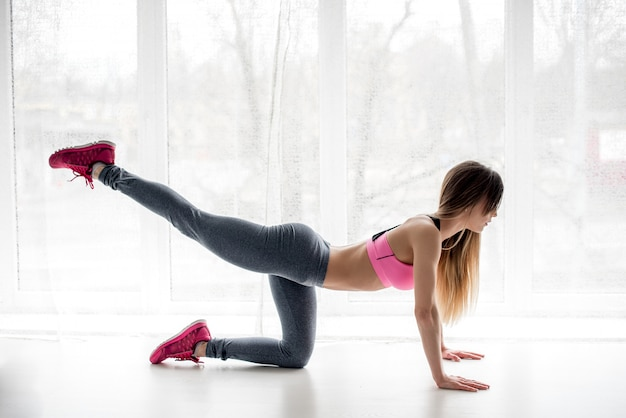 Athlète de fitness sexy effectue des exercices sur les fesses en studio. la musculation