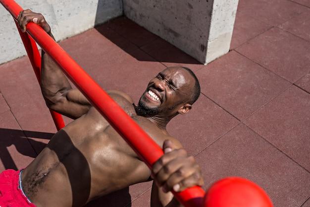 Athlète en forme faisant des exercices au stade. homme afro en plein air à la ville. faites des exercices de sport. remise en forme, santé, concept de mode de vie