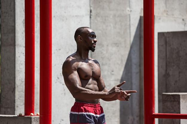 L'athlète en forme faisant des exercices. homme afro ou afro-américain en plein air à la ville. faites des exercices de sport.