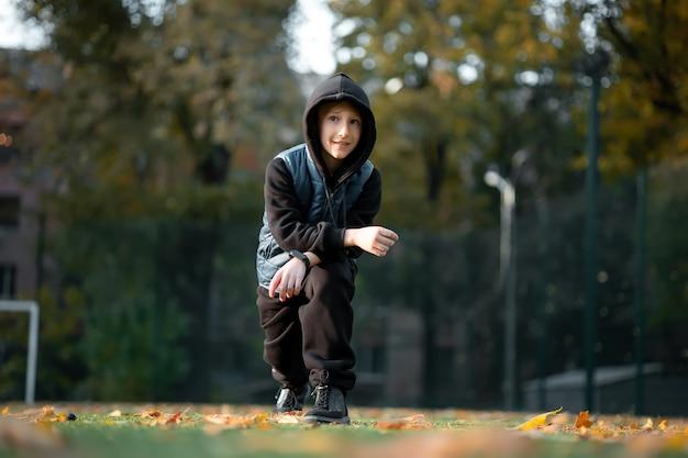 Athlète de garçon faisant l'échauffement au stade en automne