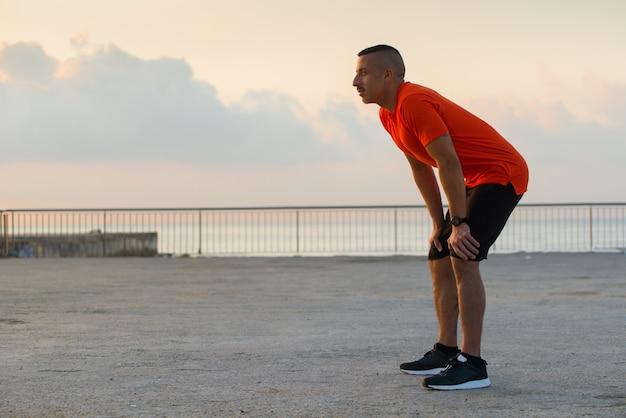 L'athlète grave récupère le souffle après le jogging