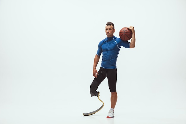 Athlète handicapé ou amputé sur fond de studio blanc, basket-ball