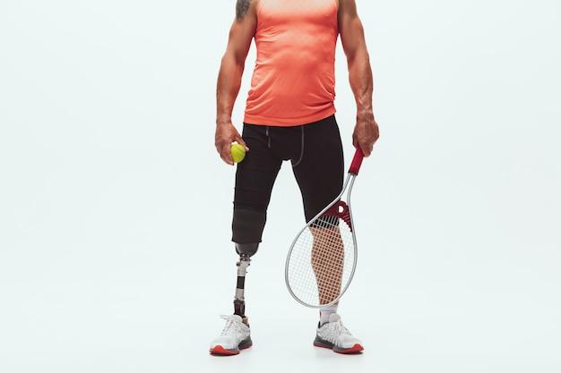 Athlète handicapé ou amputé isolé sur blanc. joueur de tennis masculin professionnel avec formation de prothèse de jambe