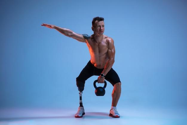 Athlète handicapé ou amputé isolé sur fond bleu studio. sportif masculin professionnel avec formation de prothèse de jambe avec des poids en néon.