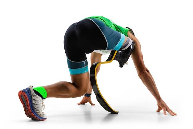 Athlète handicapé ou amputé isolé sur fond de studio blanc. coureur professionnel masculin avec formation de prothèse de jambe et pratiquant en studio. sport handicapé et concept de mode de vie sain.