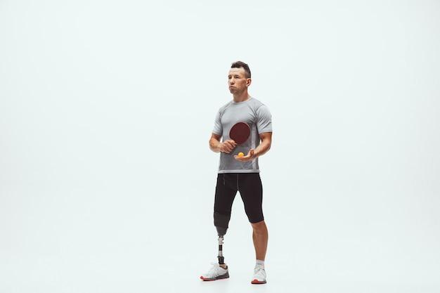 Athlète handicapé ou amputé isolé sur fond de studio blanc. joueur de tennis de table masculin professionnel avec formation de prothèse de jambe en studio. sport handicapé et concept de mode de vie sain.