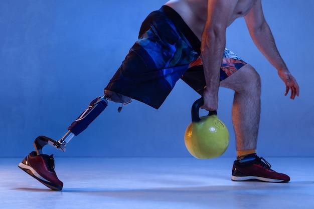 Athlète handicapé ou amputé isolé sur mur bleu.
