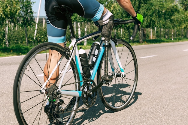 Athlète handicapé ou amputé s'entraînant au cyclisme par une journée d'été ensoleillée. sportif masculin professionnel avec prothèse de jambe pratiquant à l'extérieur. sport handicapé et concept de mode de vie sain.