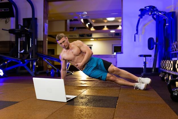 Athlète homme blond effectue des exercices de remise en forme dans la salle de sport tout en apprenant en ligne avec un ordinateur portable