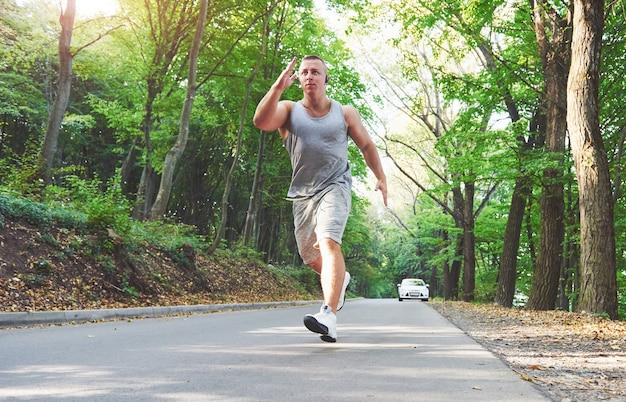 Athlète homme fitness jogging dans la nature pendant le coucher du soleil.