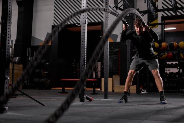 Athlète homme s'entraînant avec corde, cordes de combat cross fit exercice seul, entraînement intense à l'intérieur, dans une salle de sport moderne. concept de motivation sportive. copiez l'espace.