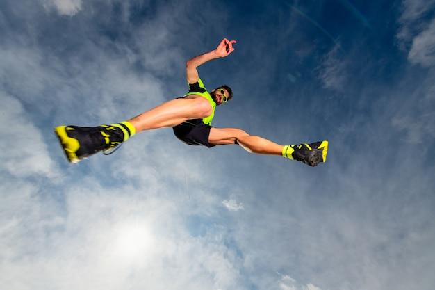 Athlète homme en sautant pendant un trail running dans les montagnes