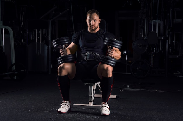 Un athlète impressionnant est assis sur un banc dans la salle de sport avec deux haltères sur ses jambes