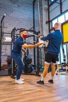Un athlète avec un instructeur dans la salle de sport faisant des exercices de bras dans la pandémie de coronavirus