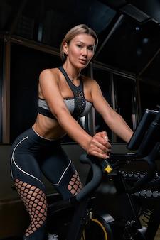 Athlète jeune femme confiante exerçant à vélo à l'intérieur. fille de fitness déterminée attrayante, faire des exercices de cyclisme dans une salle de sport sombre. entraînement fonctionnel de la fille sportive. entraînement cardiaque