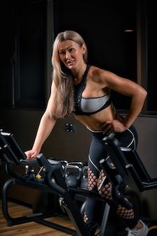 Athlète jeune femme confiante exerçant à vélo à l'intérieur. fille de remise en forme déterminée attrayante, faire des exercices de cyclisme dans une salle de sport sombre. entraînement fonctionnel de la fille sportive. entraînement cardiaque