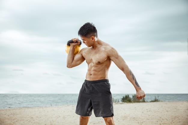 Athlète jeune homme en bonne santé faisant des squats à la plage