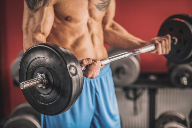 Athlète. jeune homme avec un tatouage sur une poitrine travaillant avec des haltères dans une salle de sport