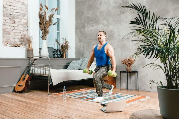 Un athlète joyeux aux cheveux noirs se fend avec des haltères dans la chambre, entraînement en ligne