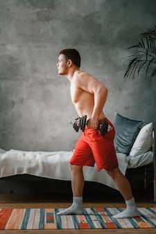 Un athlète joyeux aux cheveux noirs se précipite avec des haltères dans la chambre. le jeune homme fait du sport à la maison.