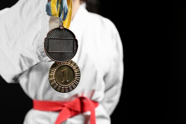 Athlète de karaté avec ceinture rouge et médailles