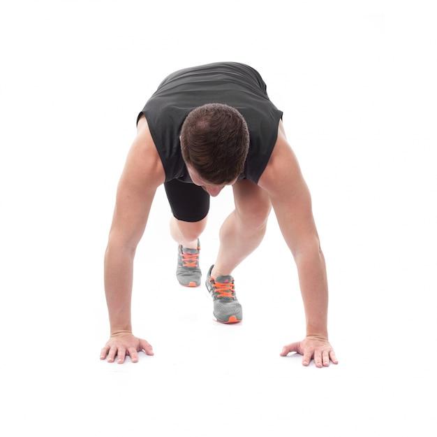 Athlète avec les mains sur le sol prêt à fonctionner