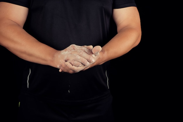 Athlète masculin adulte frotte de la poudre blanche avec de la magnésie avant des événements sportifs
