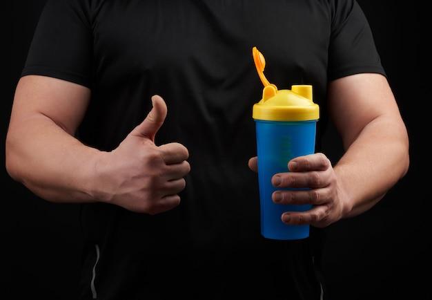 Athlète masculin adulte avec des muscles est titulaire d'une bouteille d'eau en plastique