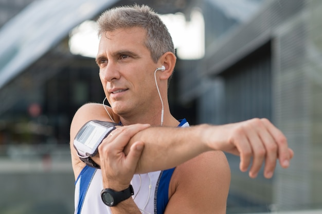 Athlète masculin d'âge mûr qui s'étend et écoute de la musique à l'extérieur