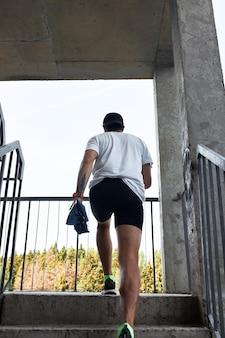 Athlète masculin concentré qui monte les escaliers pour rendre l'entraînement plus intensif