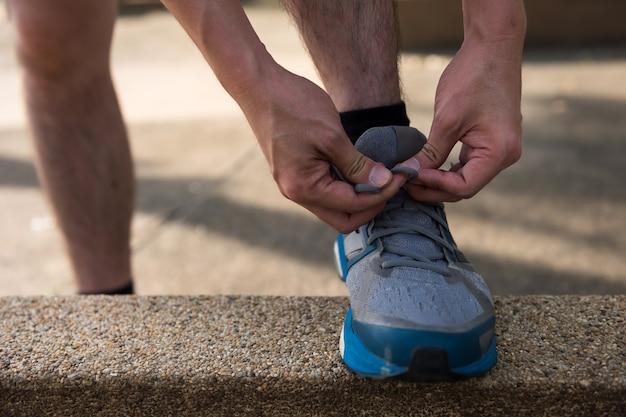 Athlète masculin coureur attachant des chaussures de course