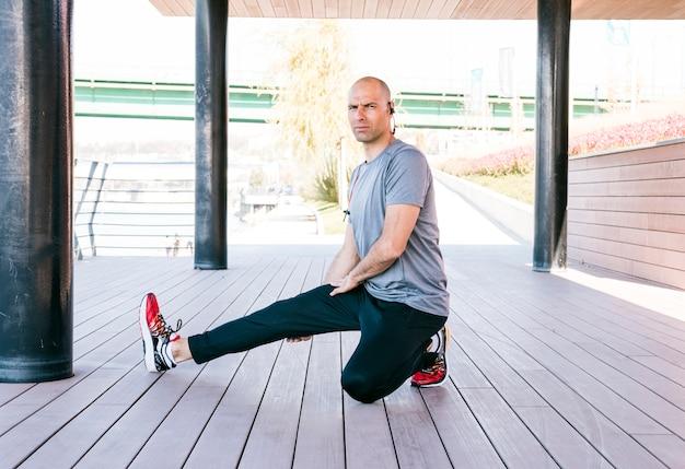 Athlète masculin faisant des exercices d'étirement avec bluetooth à l'oreille