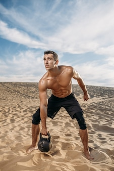 Athlète masculin faisant des exercices avec kettlebell dans le désert aux beaux jours. forte motivation dans le sport, entraînement de force en plein air