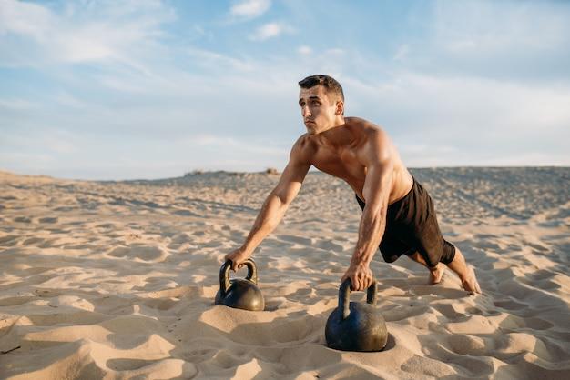 Athlète masculin faisant des exercices de push-up dans le désert
