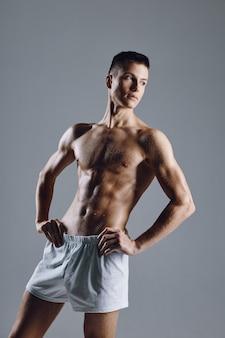 Athlète masculin fort avec les muscles des bras fléchis sur fond gris.
