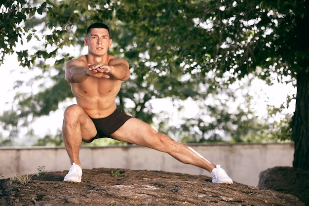 Un athlète masculin musclé faisant de l'exercice dans le parc. gymnastique, entraînement, flexibilité des entraînements de fitness.
