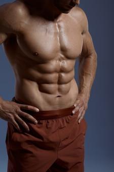 Athlète masculin musclé, séance photo en studio, fond bleu. un homme avec une carrure athlétique, un sportif torse nu en vêtements de sport, un mode de vie sain et actif
