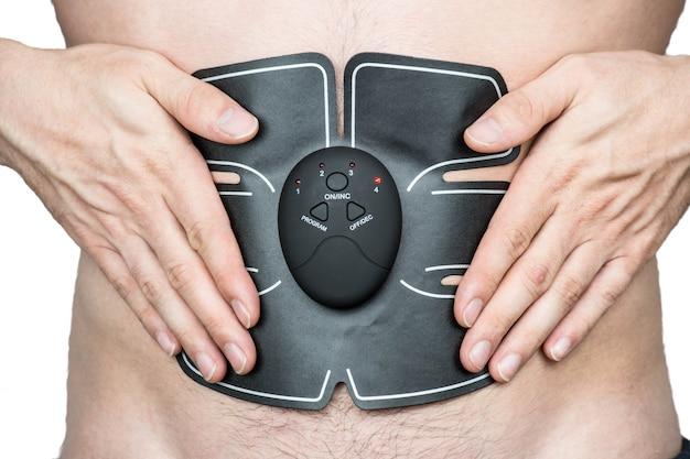 Athlète masculin portant un stimulateur musculaire ab électrique faisant des exercices abs