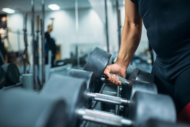 Athlète masculin prend un haltère lourd à la main, intérieur de la salle de sport.