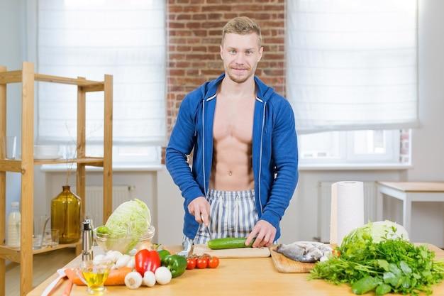 Athlète masculin prépare des aliments sains à la maison dans la cuisine