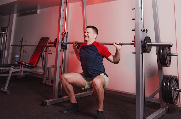 Un athlète masculin s'accroupit avec une barre dans la salle de sport avec un visage tendu. mode de vie sain
