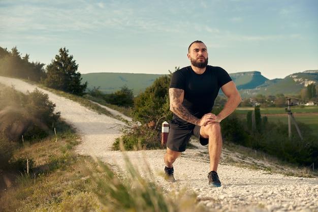 Athlète masculin s'échauffant avant de commencer à courir dans les montagnes