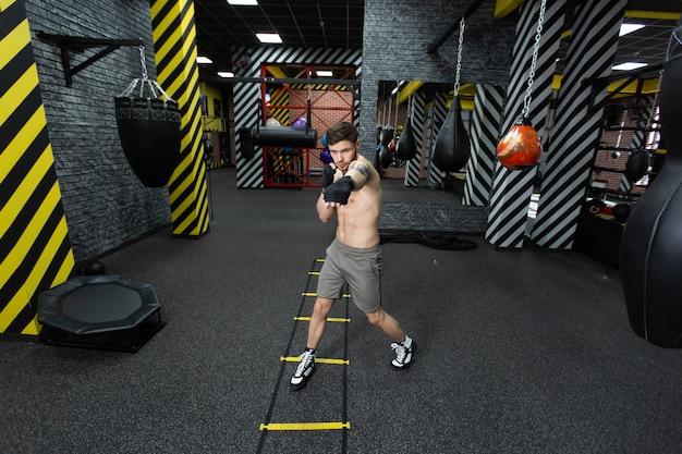 Un athlète masculin s'entraîne dans la salle de gym.