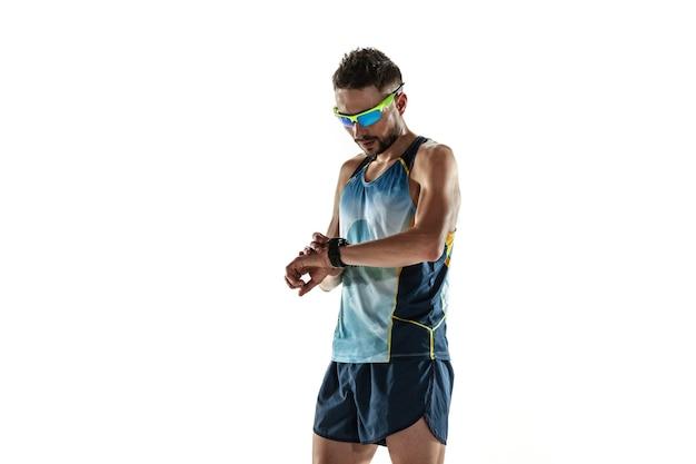 Athlète masculin de triathlon en cours d'exécution isolé sur fond de studio blanc. jogger en forme de race blanche, entraînement de triathlète portant des équipements de sport. concept de mode de vie sain, sport, action, mouvement. contrôle du temps.