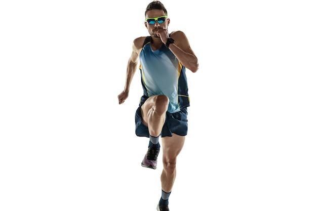 Athlète masculin de triathlon en cours d'exécution isolé sur fond de studio blanc. jogger en forme de race blanche, entraînement de triathlète portant des équipements de sport. concept de mode de vie sain, sport, action, mouvement. en saut.